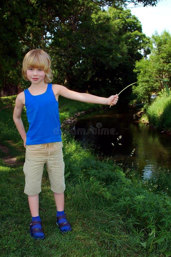 Jongen dichtbij rivier stock fotografie