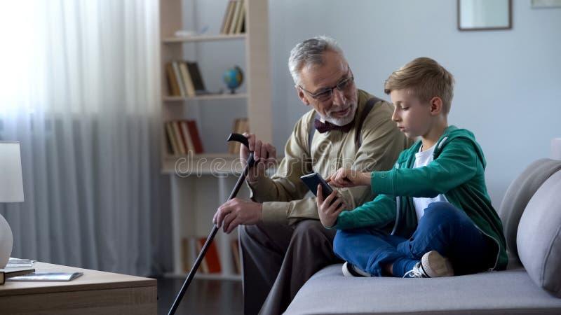 Jongen die aan de oude mens verklaren hoe te celtelefoon, eenvoudige technologieën voor de oude mens te gebruiken stock fotografie