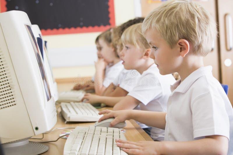 Jongen die aan een computer bij lage school werkt royalty-vrije stock fotografie