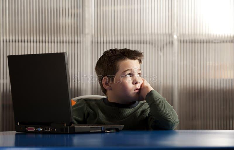 Jongen die aan een laptop computer werkt stock foto's
