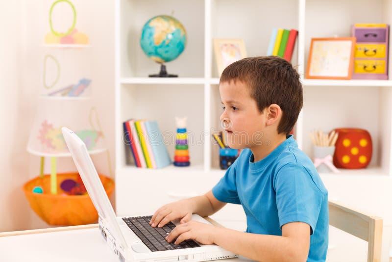 Jongen die of aan laptop computer speelt werkt stock afbeeldingen