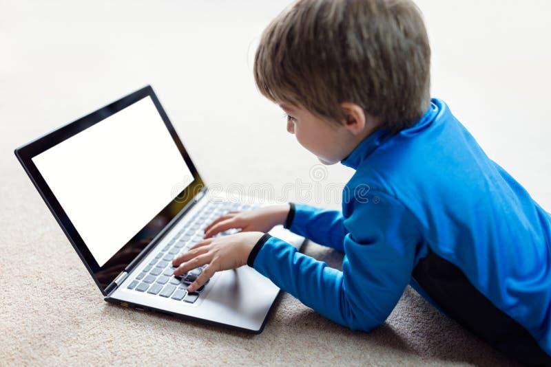 Jongen die aan laptop computer werken stock afbeelding