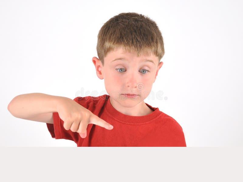 Jongen die aan Leeg Voorwerp op Witte Achtergrond richten stock afbeelding