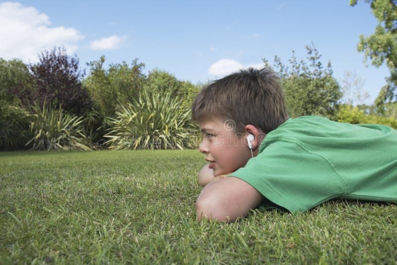 Jongen die aan MP3 Speler op Gras luisteren  royalty-vrije stock foto's