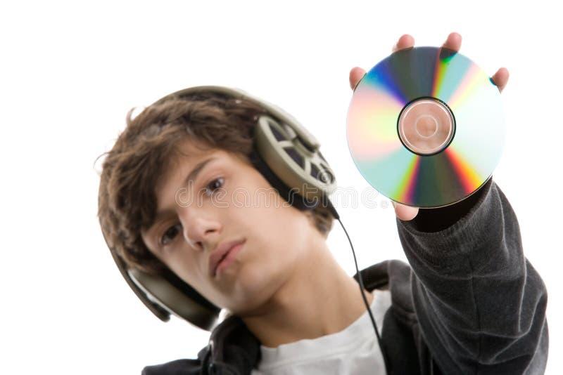 Jongen die aan muziek luistert die CD toont stock foto