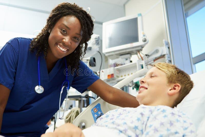 Jongen die aan Vrouwelijke Verpleegster In Emergency Room spreken stock fotografie