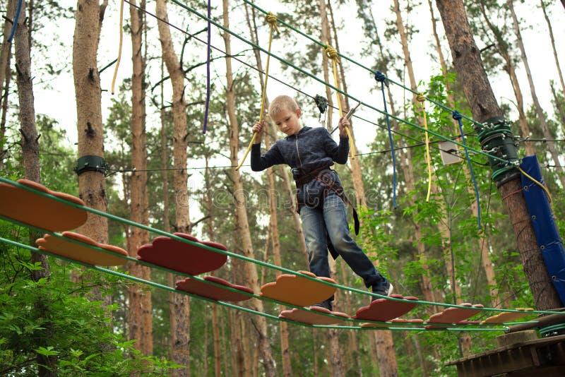 Jongen die bij avonturenpark beklimmen stock foto