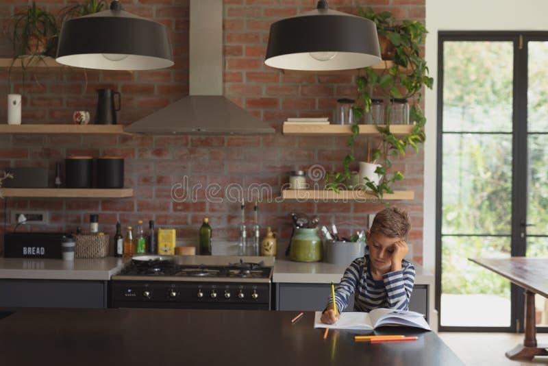 Jongen die bij lijst in keuken thuis bestuderen royalty-vrije stock fotografie