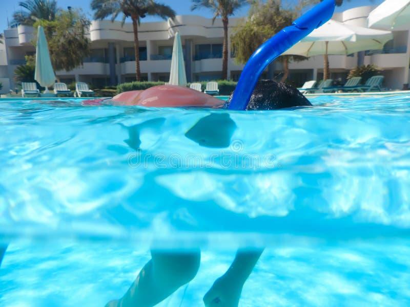 Jongen die bij pool met masker zwemmen stock foto
