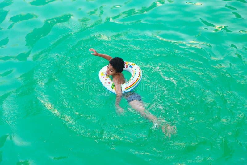 Jongen die bij pool zwemmen stock afbeelding