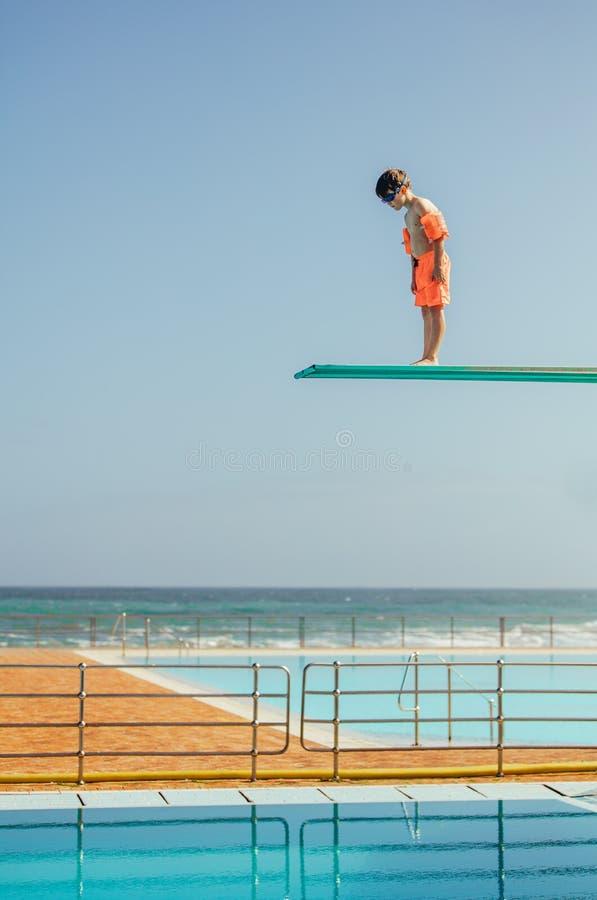 Jongen die bij zwembad leert te duiken stock fotografie