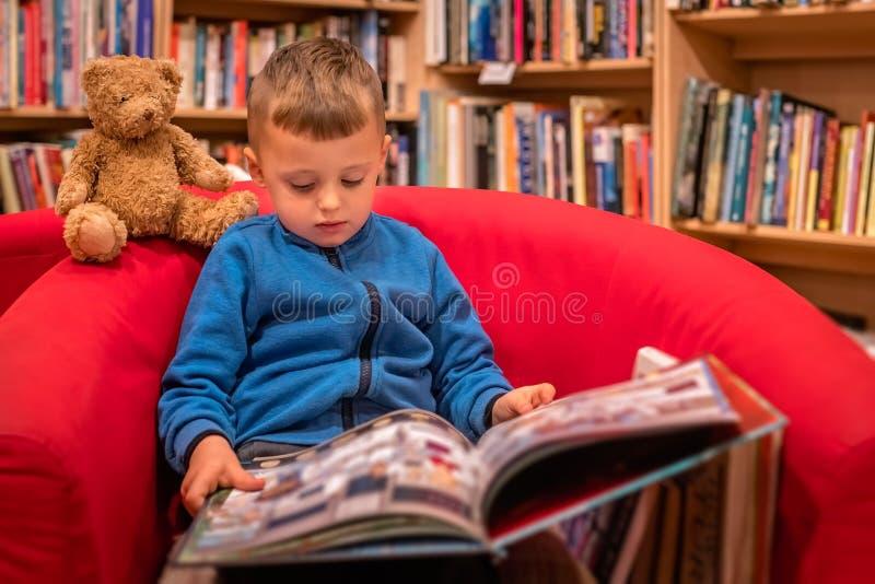 Jongen die boek in een boekhandel doorbladert stock afbeeldingen