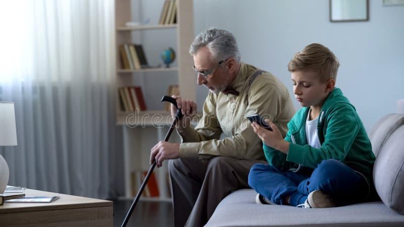 Jongen die celtelefoon, verstoorde opazitting met behulp van opzij, Internet-verslavingsconcept stock foto's