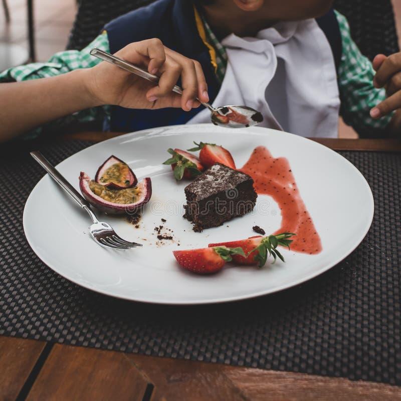 Jongen die chocoladebrownie en bessen eten stock fotografie
