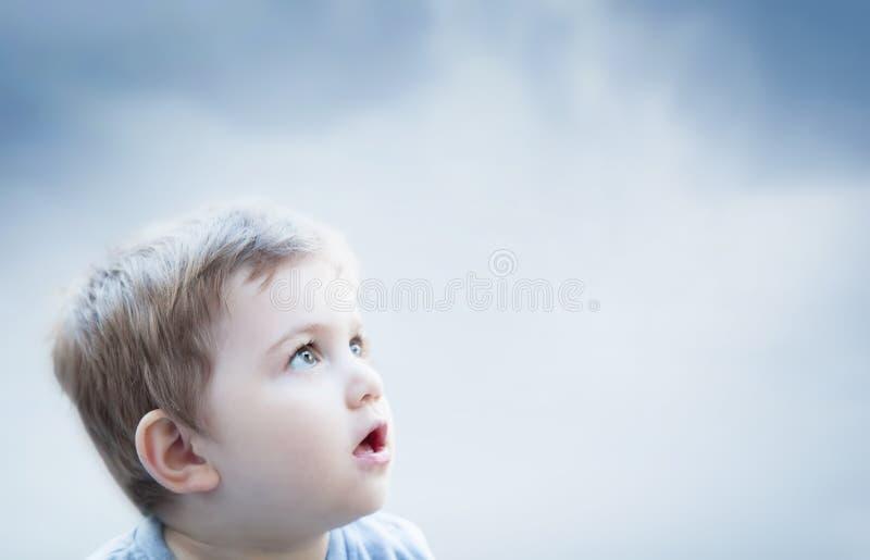Jongen die de hemel met verraste uitdrukking bekijken Kindverbeelding royalty-vrije stock foto