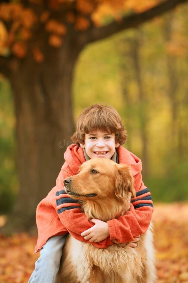 Jongen die de Hond koestert stock foto
