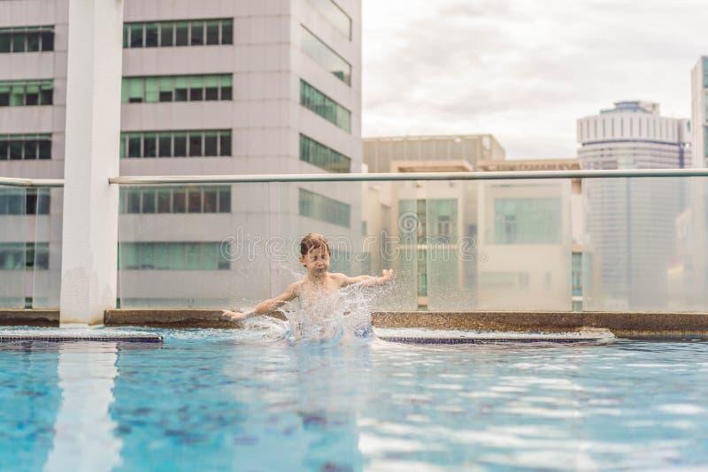 Jongen die in de pool onder de wolkenkrabbers en de grote stad springen Ontspan in de grote stad Rust van spanning royalty-vrije stock afbeelding