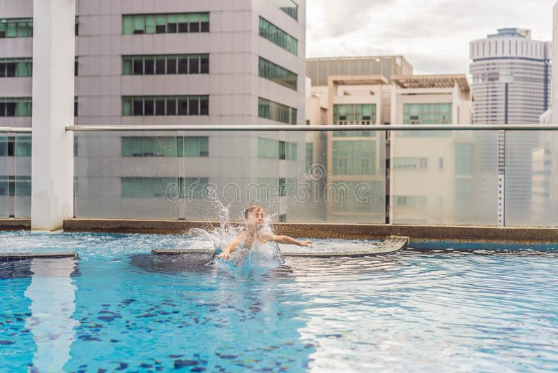 Jongen die in de pool onder de wolkenkrabbers en de grote stad springen Ontspan in de grote stad Rust van spanning stock foto