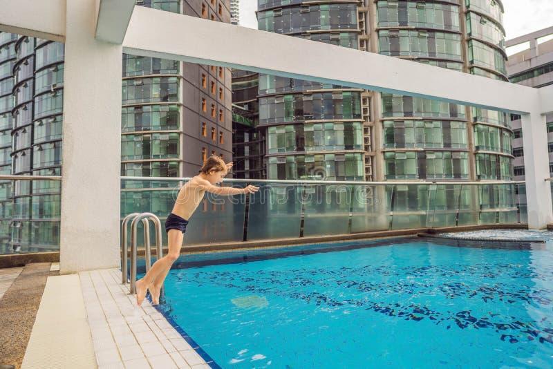 Jongen die in de pool onder de wolkenkrabbers en de grote stad springen Ontspan in de grote stad Rust van spanning stock foto's