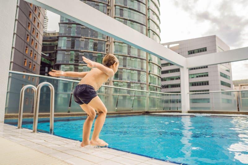 Jongen die in de pool onder de wolkenkrabbers en de grote stad springen Ontspan in de grote stad Rust van spanning royalty-vrije stock foto's