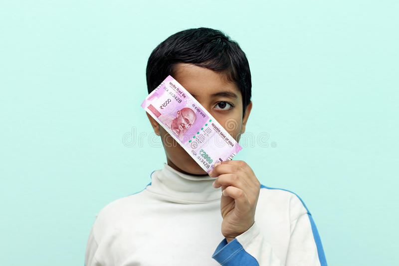 Jongen die de Roepie nieuw Indisch geld van 2000 in zijn hand houden royalty-vrije stock fotografie