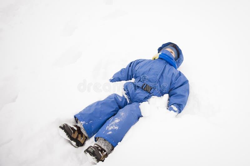 Jongen die in de sneeuw liggen royalty-vrije stock afbeelding