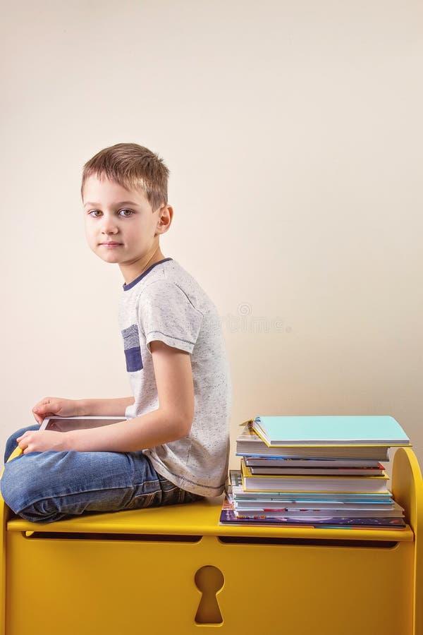 Jongen die digitale tabletzitting gebruiken dichtbij BIB-stapel boeken stock afbeelding