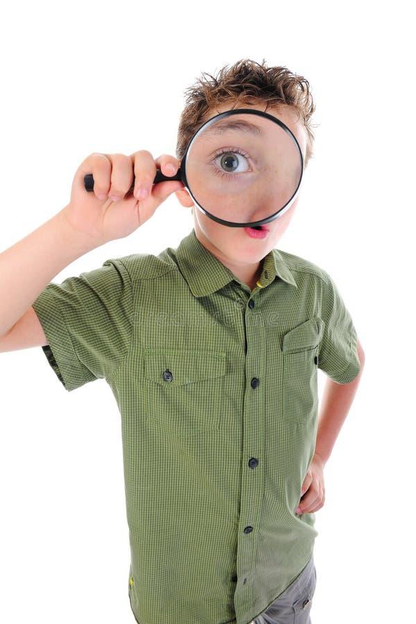 Jongen die door een vergrootglas kijkt stock afbeeldingen