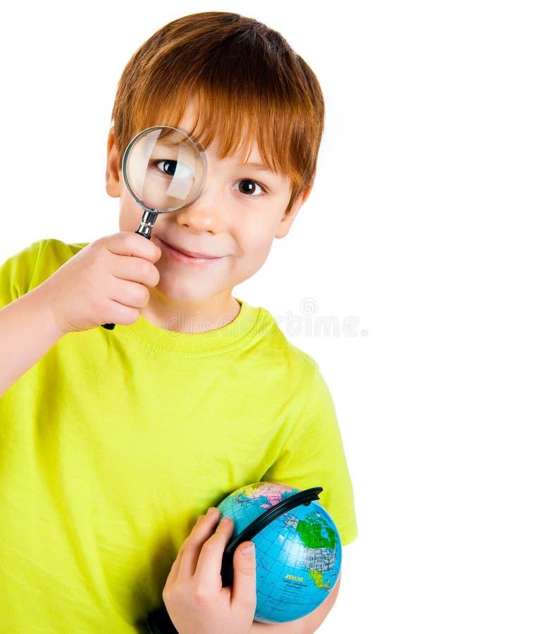 Jongen die door een vergrootglas kijkt stock afbeelding