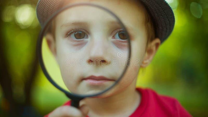 Jongen die door meer magnifier kijken stock footage