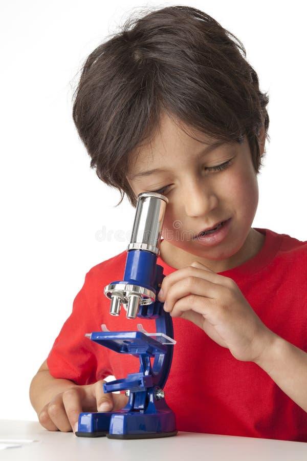 Jongen die door microscoop kijkt stock afbeeldingen