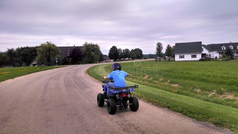 Jongen die een ATV berijden stock afbeelding