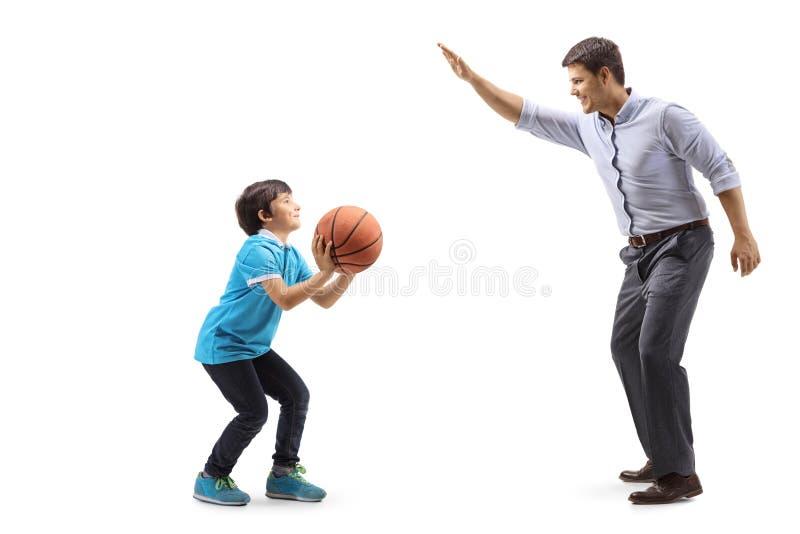 Jongen die een basketbal werpen en met zijn vader spelen royalty-vrije stock foto's