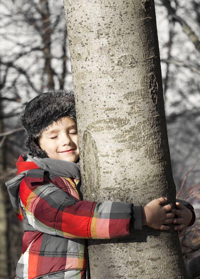 Jongen die een boom koesteren, die de geluiden van de Aard luisteren stock afbeelding