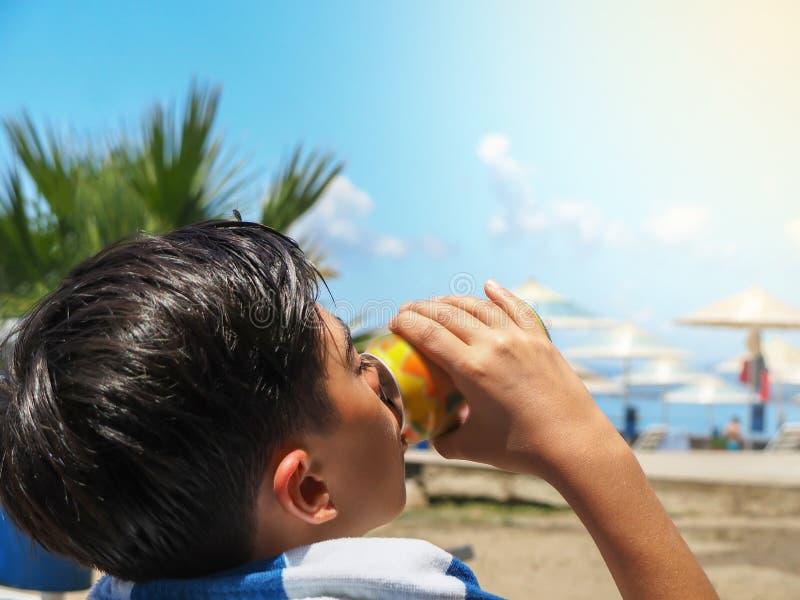 Jongen die een drank op het strand op een hete de zomerdag drinken stock afbeelding