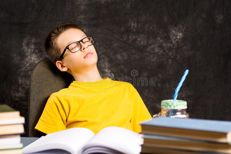 Jongen die een dutje nemen terwijl het beëindigen van thuiswerk stock fotografie