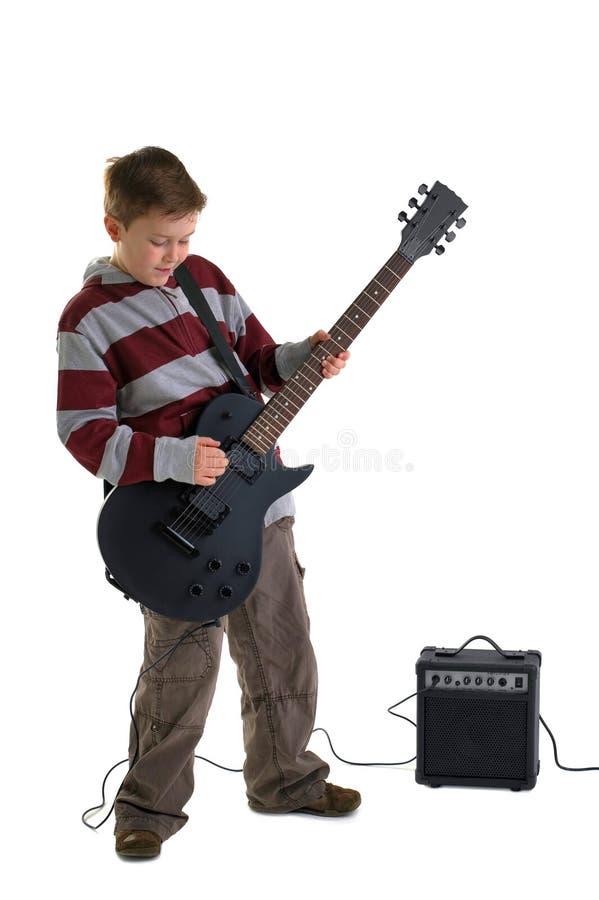Jongen die een elektrische geïsoleerde gitaar speelt stock afbeelding