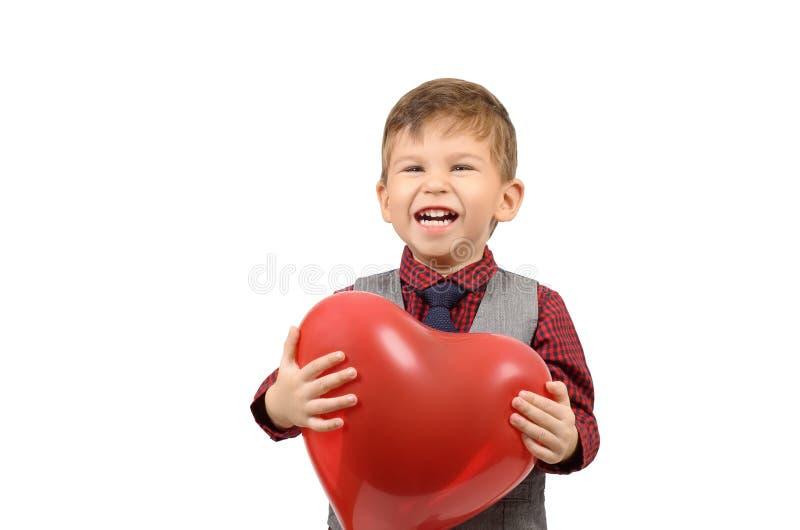 Jongen die een hart gevormde ballon houden stock foto