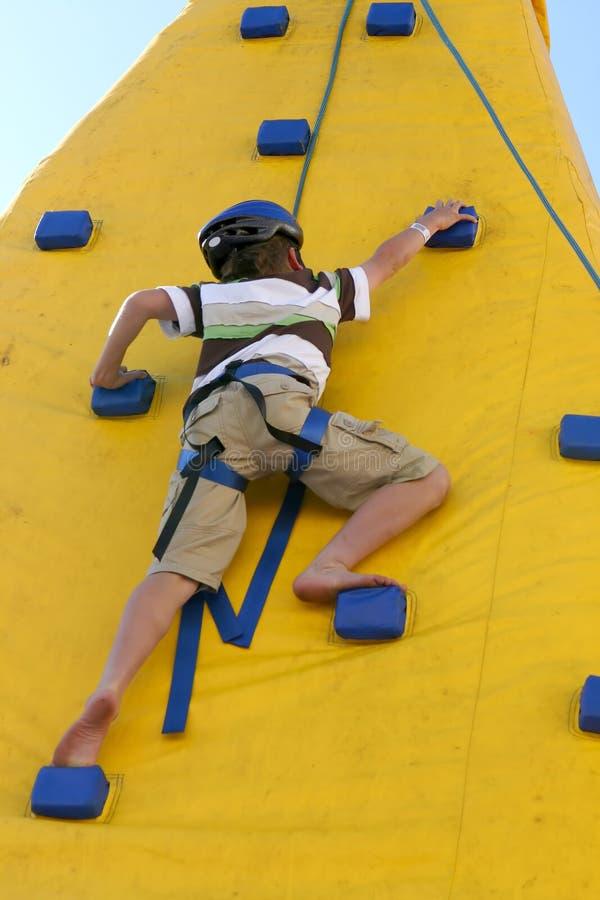 Jongen die een het beklimmen muur beklimt. royalty-vrije stock afbeelding