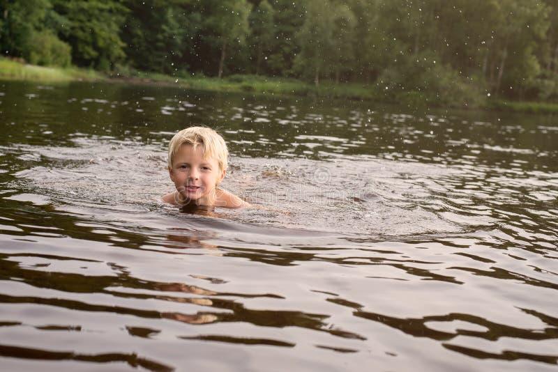 Jongen die in een meer zwemmen recente middag stock afbeelding