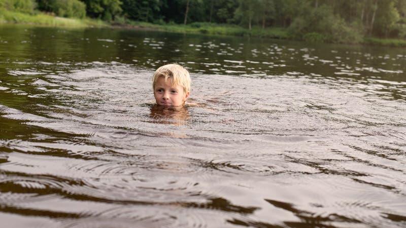 Jongen die in een meer zwemmen recente middag stock afbeeldingen