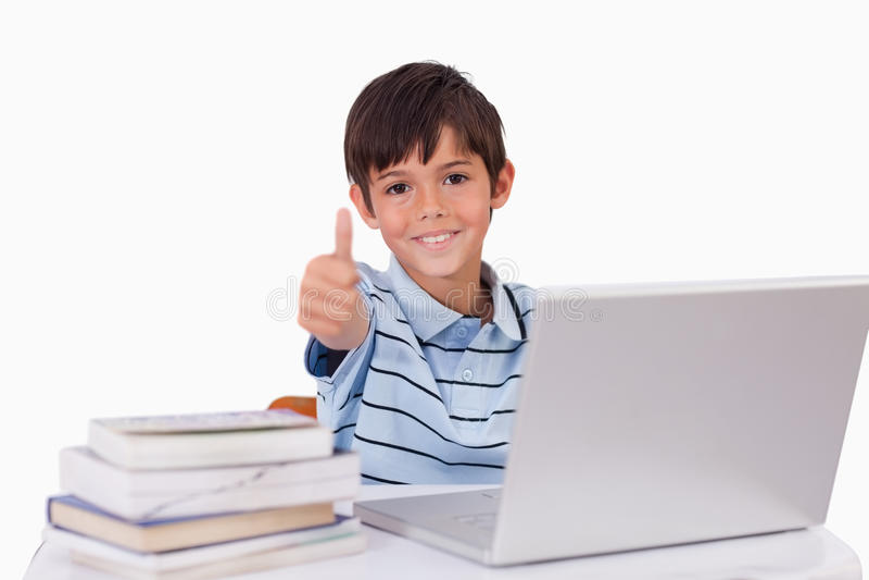 Jongen die een notitieboekje met de omhoog duim gebruikt stock fotografie