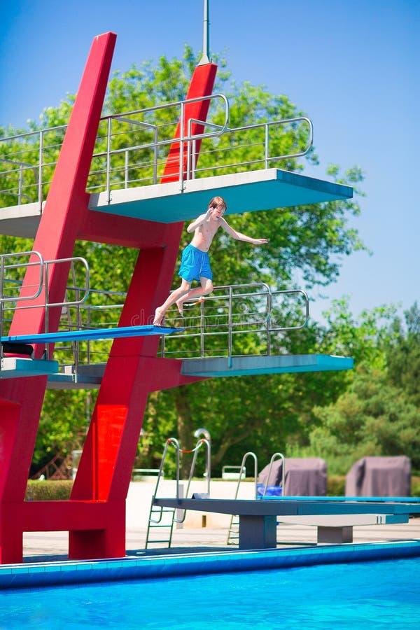 Jongen die in een pool springen royalty-vrije stock afbeeldingen