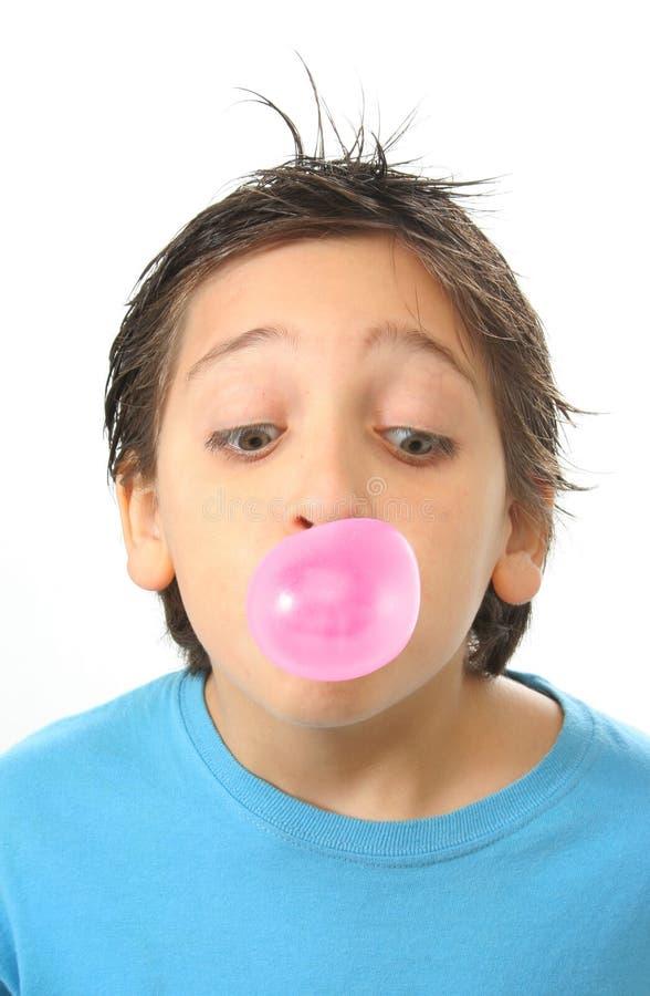 Jongen die een roze kauwgom blaast stock foto