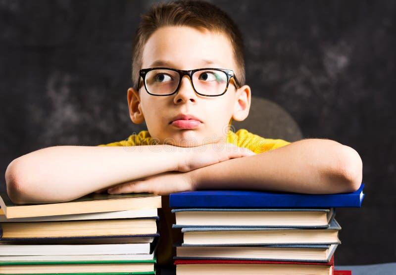 Jongen die een rust bovenop boeken nemen royalty-vrije stock foto's