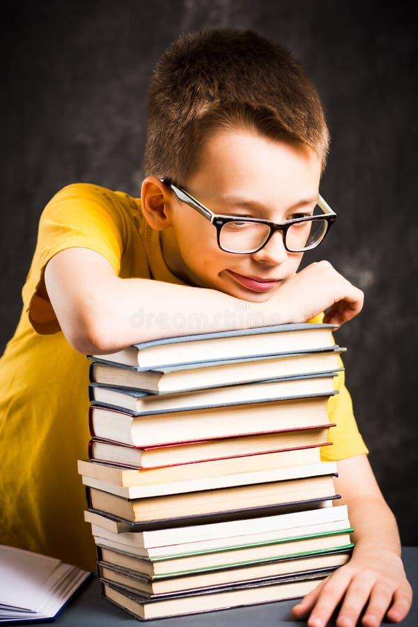 Jongen die een rust bovenop boeken nemen royalty-vrije stock afbeelding