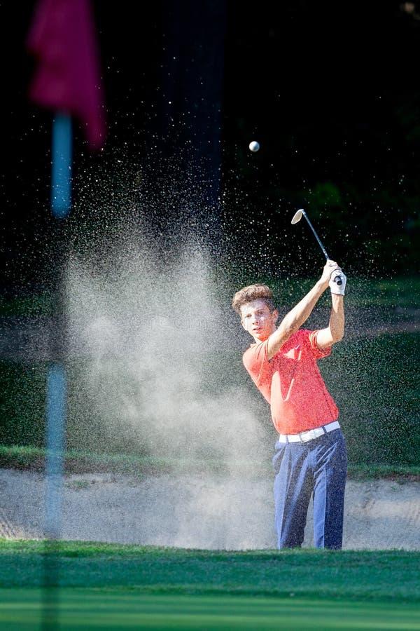 Jongen die een schot van de bunker op een golfcursus spelen royalty-vrije stock fotografie