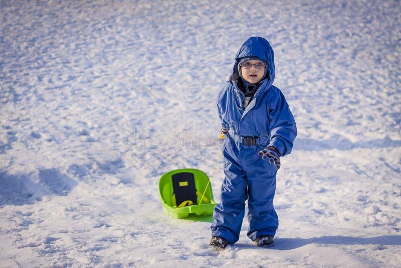 Jongen die een slee op sneeuw trekken royalty-vrije stock afbeeldingen