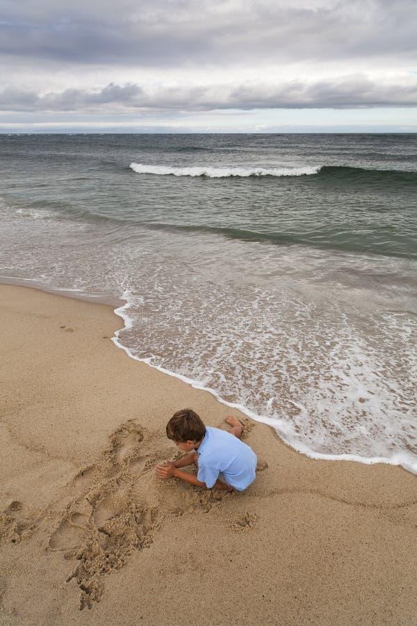 Jongen die een zandkasteel maakt stock foto's