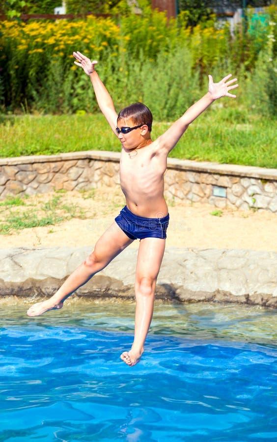 Jongen die in een zwembad springt stock afbeeldingen
